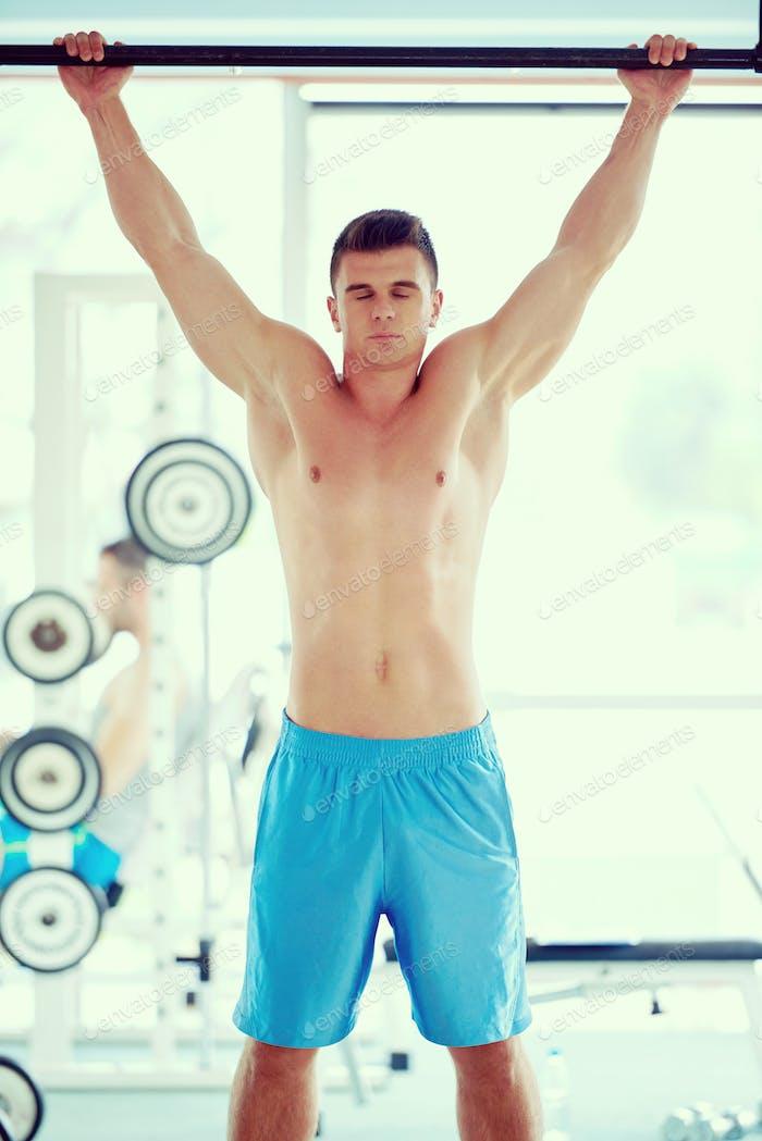 gut aussehende junge mand arbeiten aus in fitnessstudio
