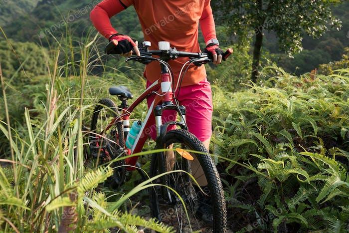 Woman mountain biker with bike on mountain top