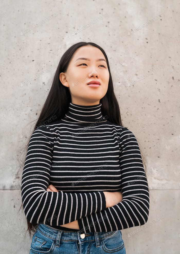 Asian woman standing against grey wall.