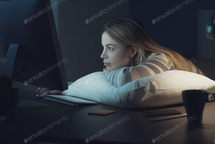 Bored woman working late at night with her computer