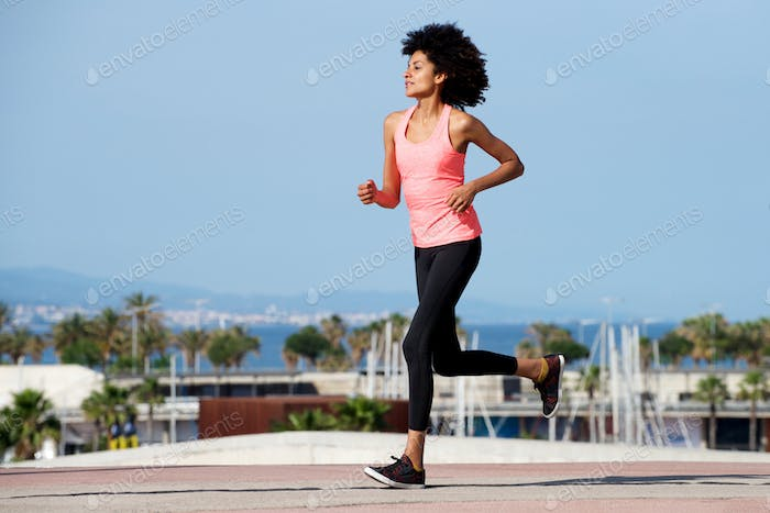 Full length female athlete training outside by sea