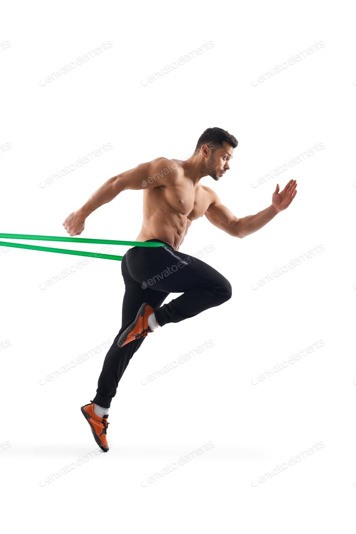 Shirtless man running in place using resistance band