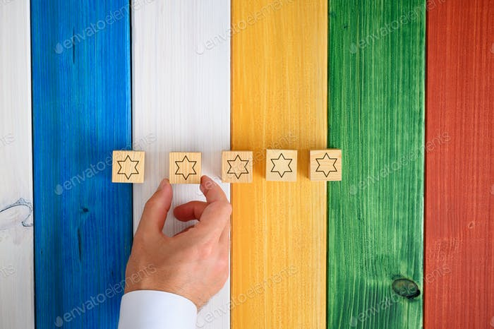 Man placing five wooden cubes with stars on them on colorful desk