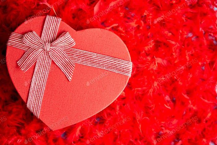 Herzförmiges Geschenk, platziert auf roten Federn Hintergrund