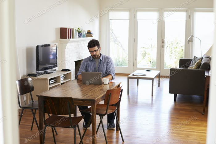 Man Working From Home Using Laptop On Dining Table