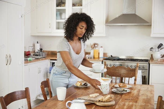 Teenage Girl Clearing Breakfast Table And Loading Dishwasher