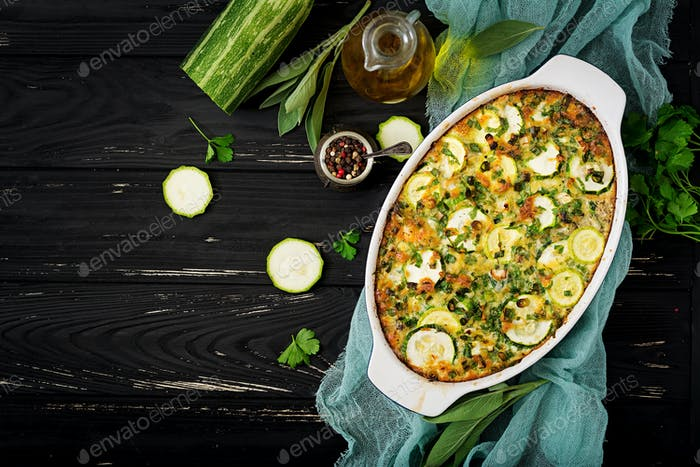 Zucchini casserole with eggs, milk, cheese and greens herbs. Flat lay. Top view