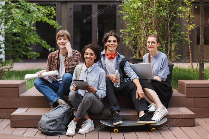 Group of cool smiling students sitting and happily looking in camera while spending time together