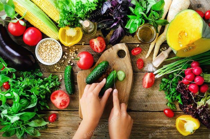 Frau Hände schneiden Gemüse auf hölzernem Hintergrund. Gemüse Kochzutaten, Draufsicht, Kopie