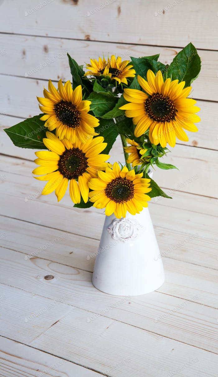 A bouquet of autumn sunflowers in a vase on a wooden table