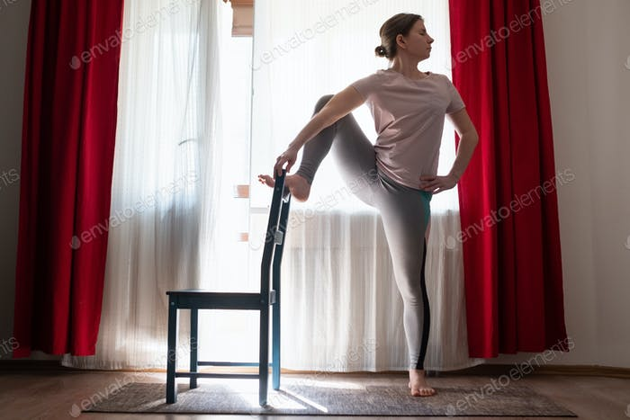 Young woman doing yoga doing lone raised leg balance using chair.