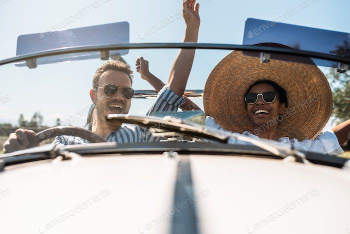 Multiracial pareja en un convertible vintage coche