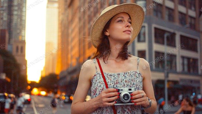 Chica atractiva con una cámara retro en la ciudad