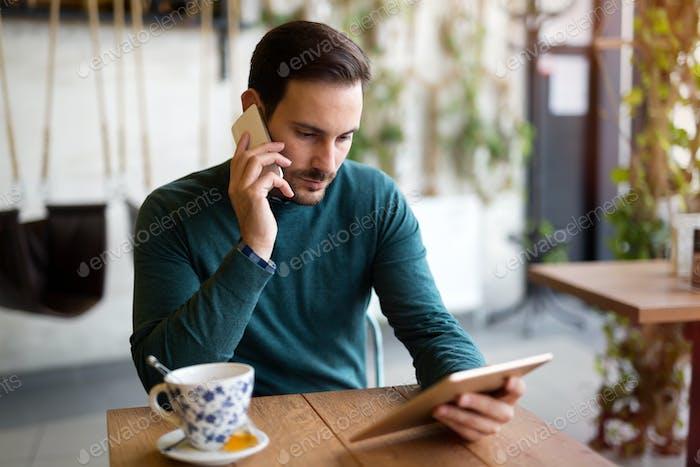 Junger attraktiver Mann mit digitalem Tablet im Café