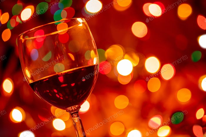 Red wine glass against christmas lights bokeh background