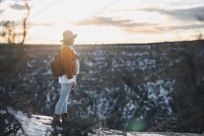 Joven excursionista con una mochila en el atardecer