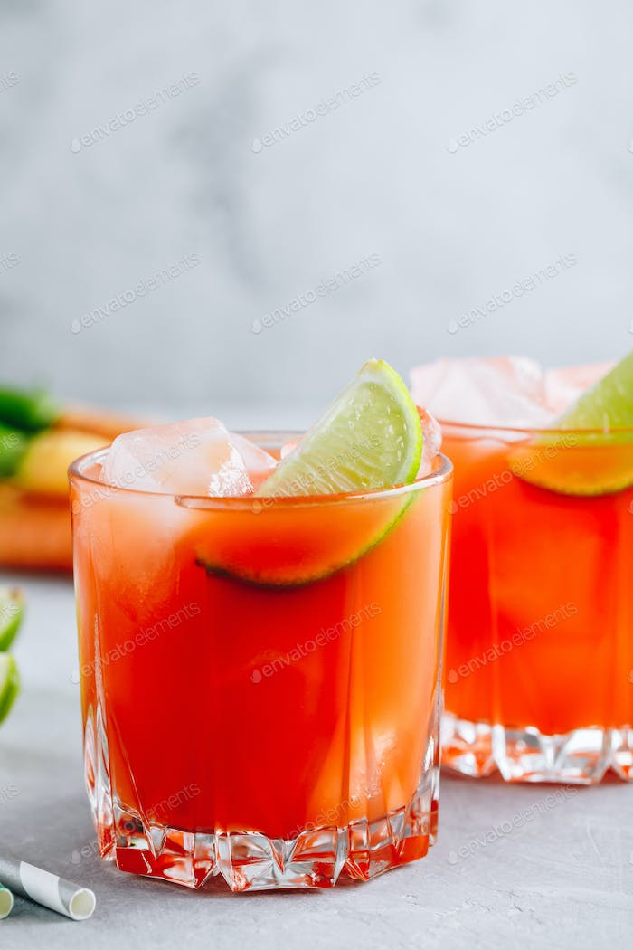 Carrot Ginger Margarita cocktail with lime in glass
