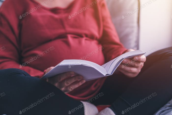 Pregnant woman reading book in living room