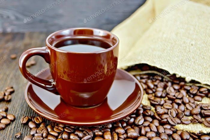 Kaffee in brauner Tasse mit Körnern und Beutel an Bord