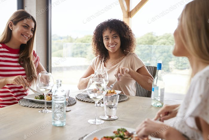 Multi ethnic group of three happy young adult women eating and talking during a dinner party