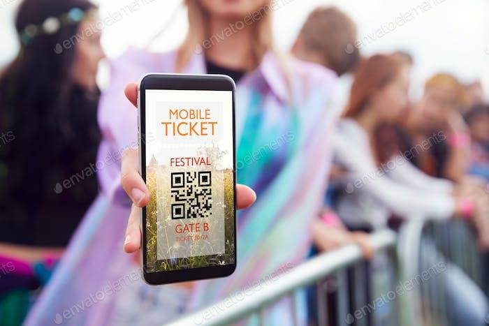 Nahaufnahme der Frau hält Handy-Bildschirm zu Kamera, als Sie bei Eingang zum Musikfestival ankommt