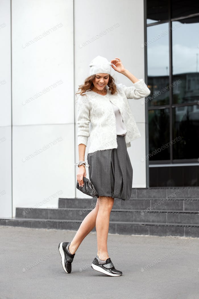 Stylish girl dressed in the fashionable gray skirt, white blouse, white hat and sneakers poses in