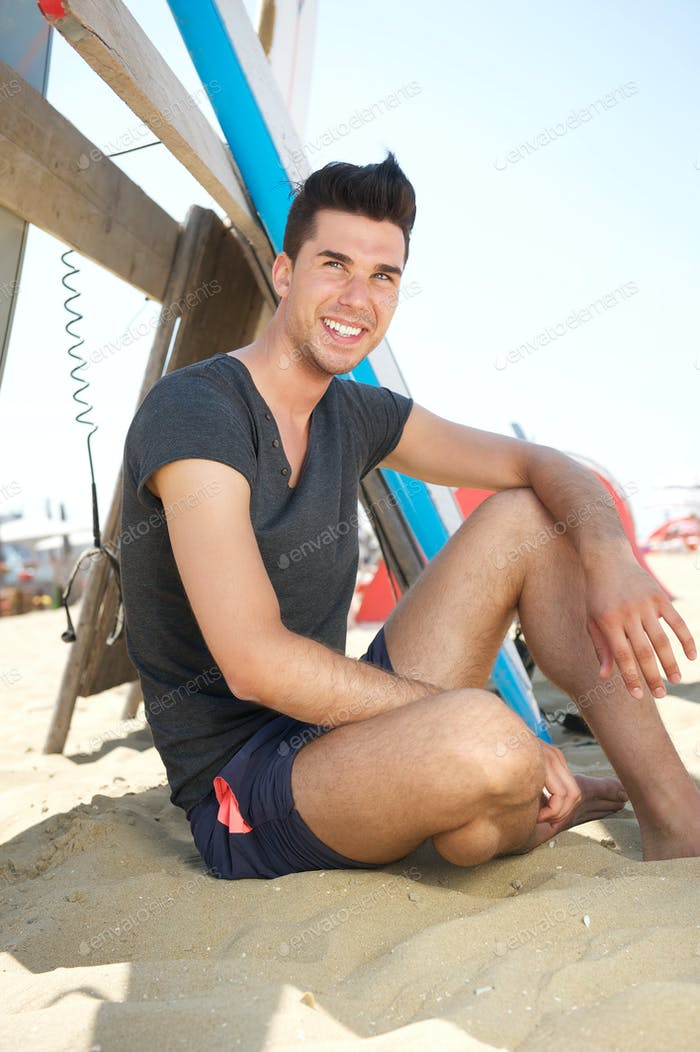Happy young man sitting at the beach with surf board