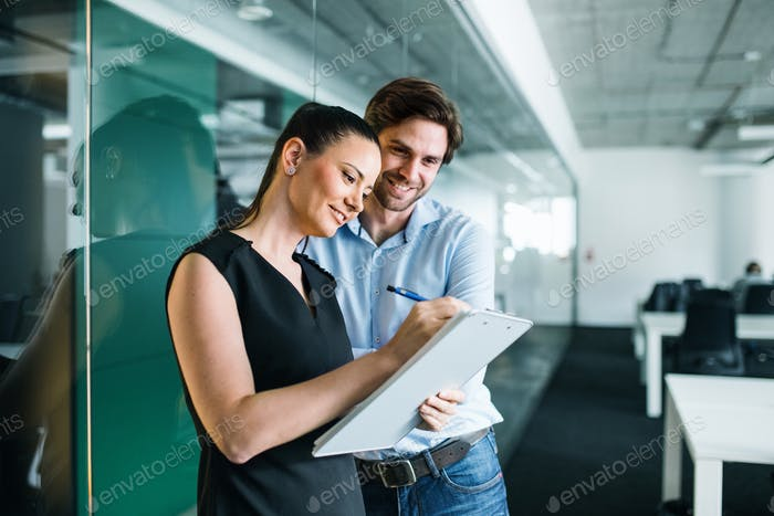 Young businesspeople with clipboard in an office, working