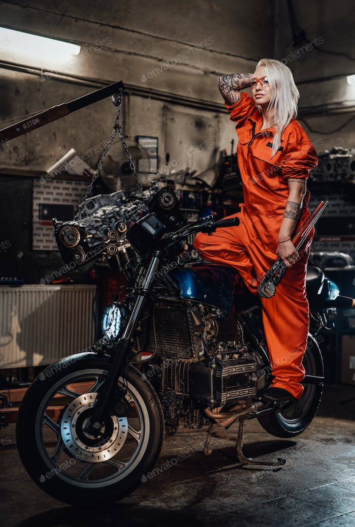Beautiful female mechanic in orange overalls hold a big wrench and posing for a camera in garage