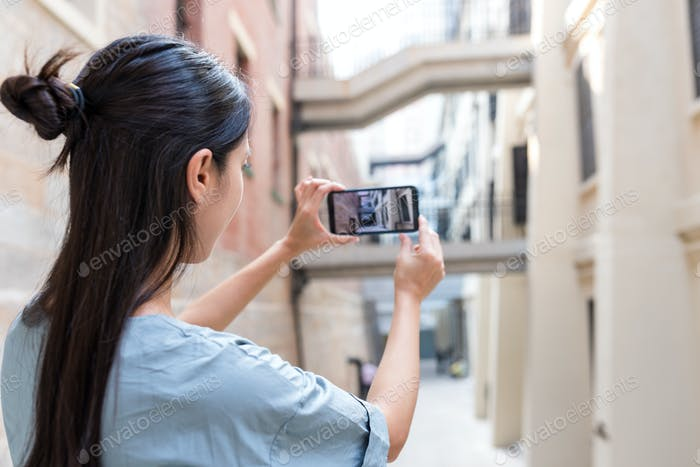 Woman tourist taking photo on cellphone