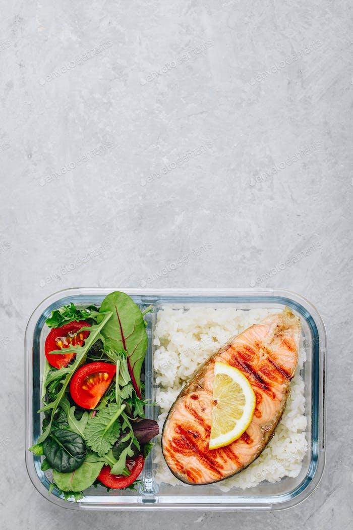Meal Prep Behälter mit Lachs und Reis, grüne Mischung Salat mit Tomaten.