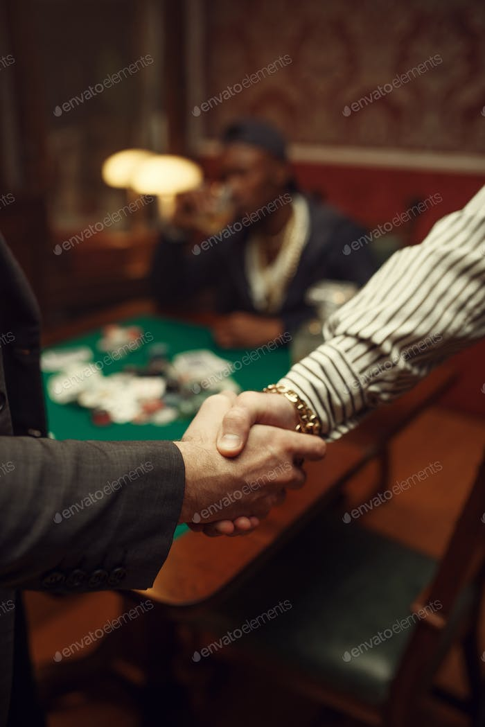 Male poker players shake hands in casino