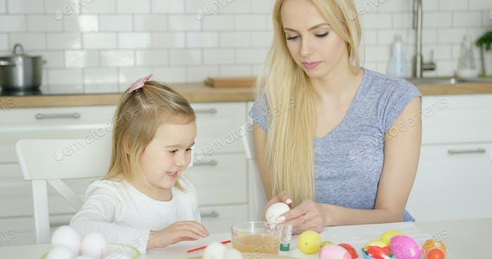 Chica Alegre pintura huevos con madre