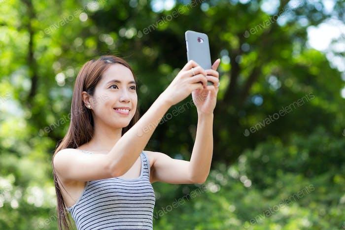 Женщина снимает фотографию с помощью мобильного телефона