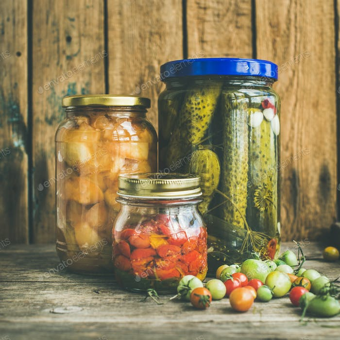 Autumn seasonal pickled vegetables and fruit in jars, square crop