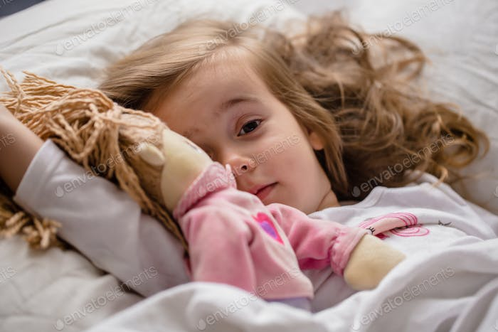 little girl falls asleep in bed with soft doll white