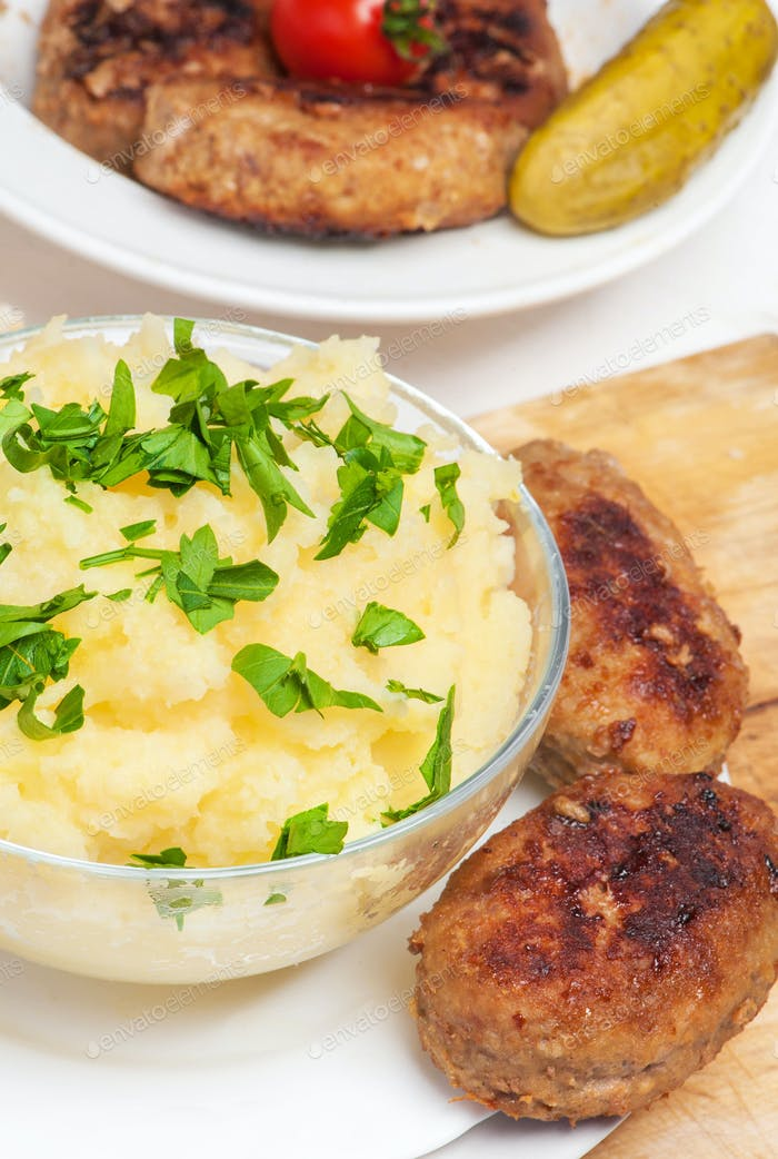 Meat patties with mashed potatoes and fresh vegetables.