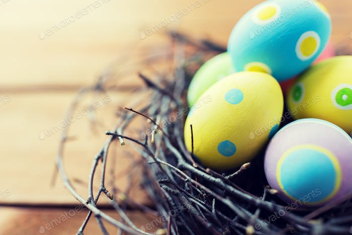 close up of colored easter eggs in nest on wood