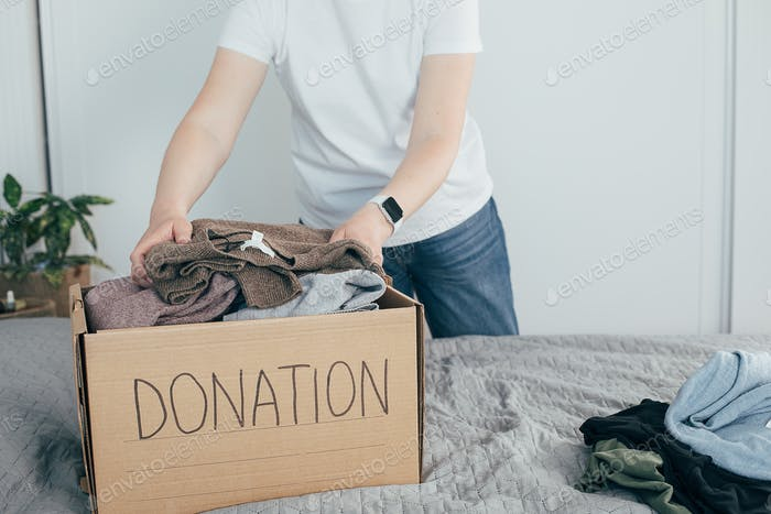 Donation box with clothes. Woman preparing clothing for donation
