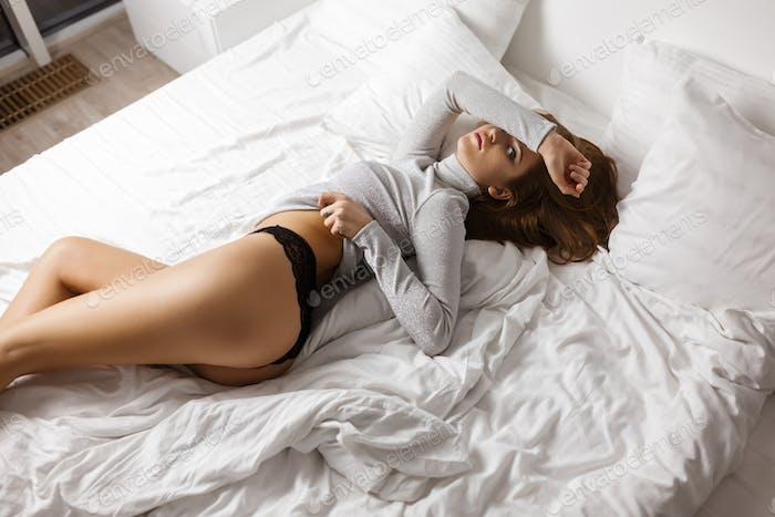 Beautiful woman in sweater and black lingerie lying in bad and thoughtfully looking in camera