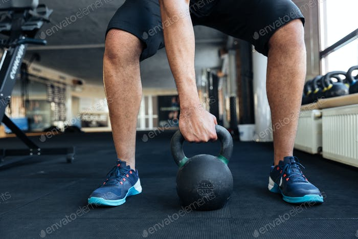 Bodybuilder using kettlebell in his workout at the gym