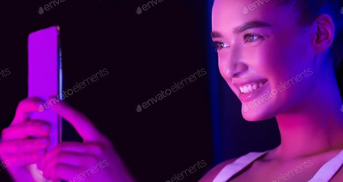 Excited woman taking selfie on phone, illuminated by pink light