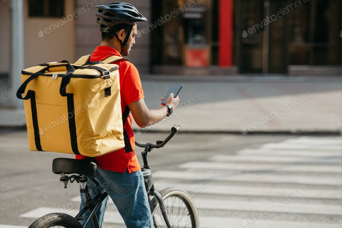 Delivery man on bicycle. Guy with backpack and helmet stopped at intersection and looked at phone