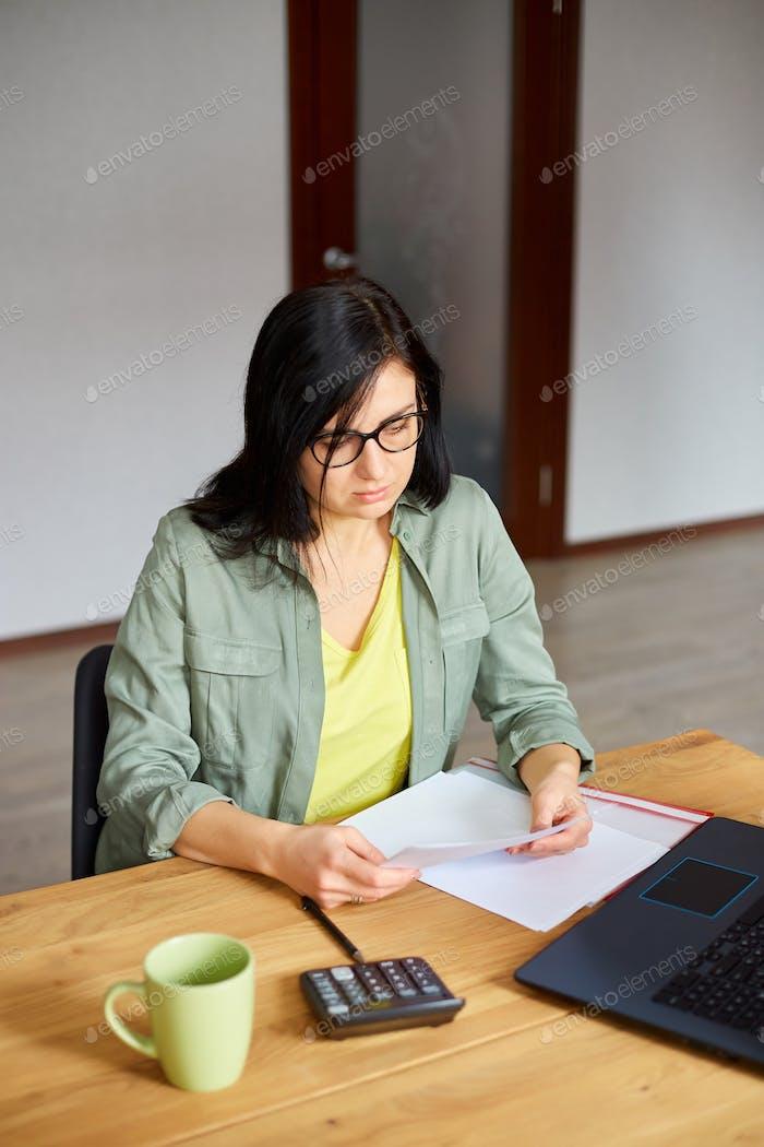 Mujer morena elegante en gafas sentado en la mesa de madera con bloc de notas trabajando en su oficina