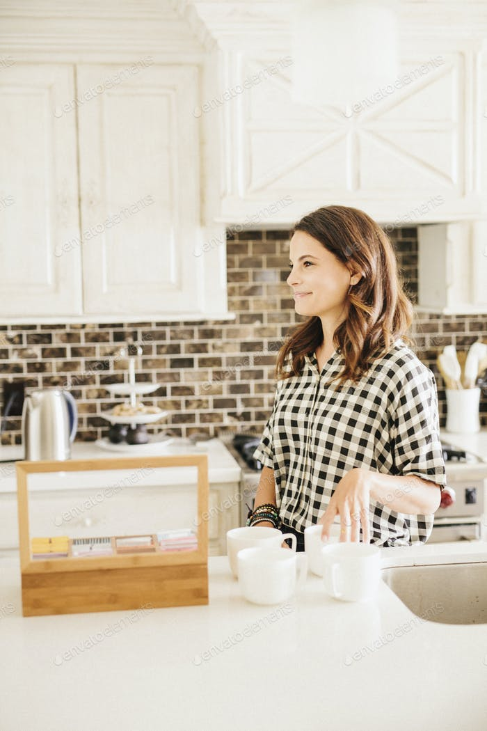 Woman with long brown hair, wearing a chequered shirt, standing in a kitchen, making a cup of tea.