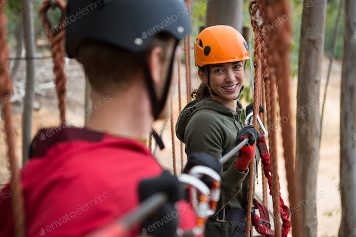 Smiling young woman looking at man while crossing zip line