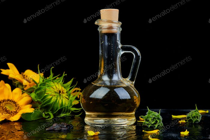 Sunflower oil in glass jar, seeds and flowers