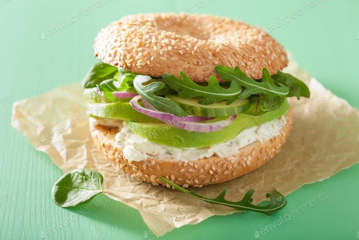 avocado sandwich on bagel with cream cheese onion cucumber arugu