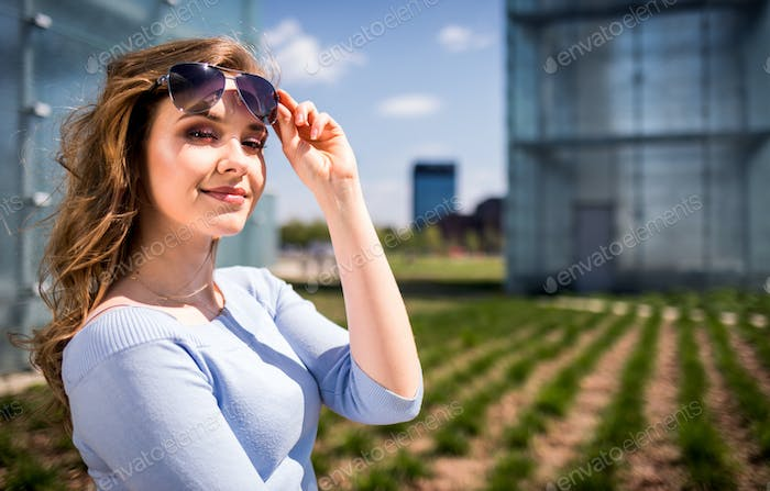 Happy young woman among modern architecture having fun during summer