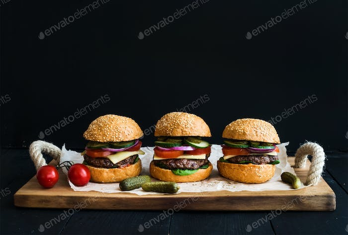 Fresh beef burgers with cheese, vegetables, pickles and spicy tomato sauce
